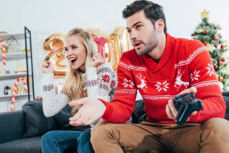beautiful couple playing video game with joy pads on christmas eve