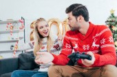 young couple playing video game with joysticks on christmas eve
