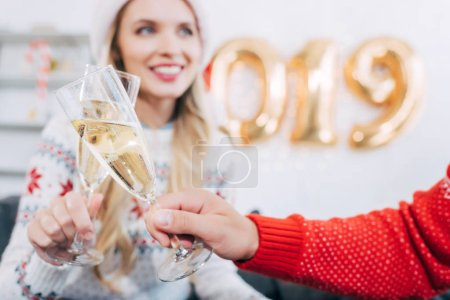 selective focus of couple clinking with champagne glasses and celebrating 2019 new year