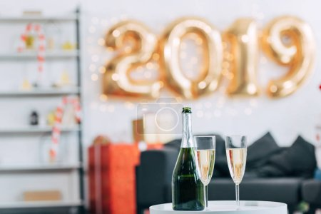 champagne bottle and glasses with 2019 new year balloons on background