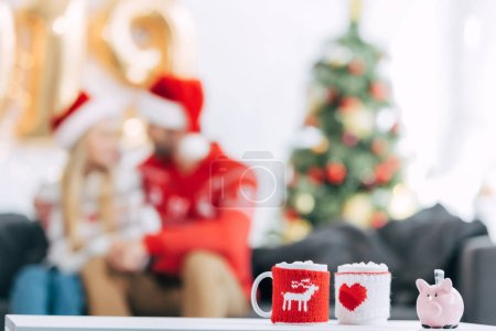 christmas cocoa cups with marshmallow and piggy bank with banknote on table, couple sitting behind