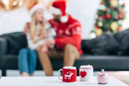 christmas coffee cups and piggy bank with banknote on table, couple sitting behind