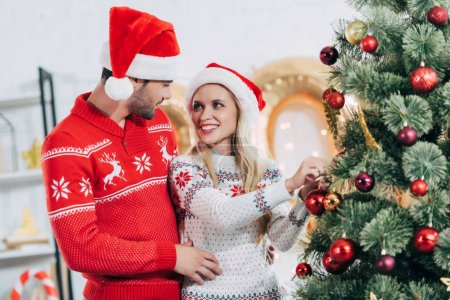 young happy couple decorating christmas tree together