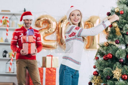 happy woman decorating christmas tree while man carrying gifts