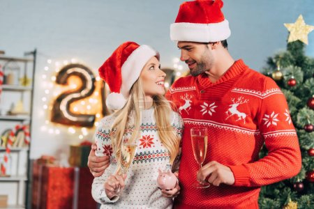 couple in santa hats with champagne glasses holding piggy bank with savings for christmas