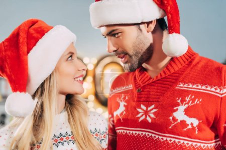 Foto de Pareja feliz con sombreros de santa mirando el uno al otro en la Nochebuena - Imagen libre de derechos