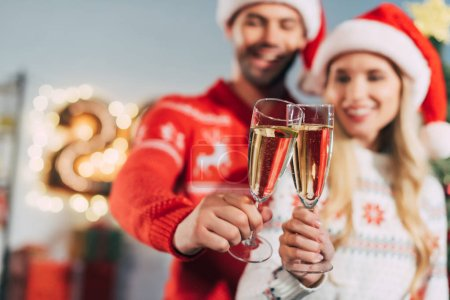 selective focus of couple clinking with champagne glasses and celebrating new year