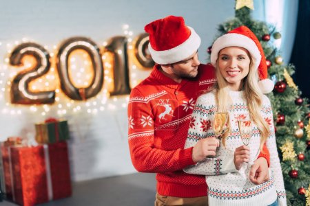happy couple in santa hats clinking with champagne glasses and celebrating 2019 new year