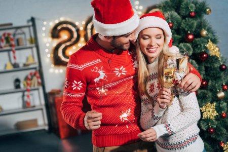 Foto de Pareja en santa sombreros tintinear con copas de champán y celebrar la Navidad - Imagen libre de derechos