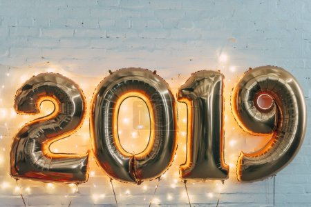 2019 golden balloons with light garland on white wall for new year