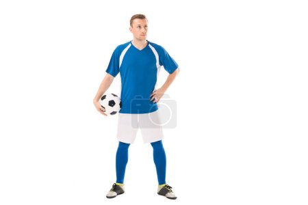 Photo for Confident young soccer player holding ball and looking away isolated on white - Royalty Free Image