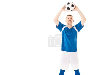 Photo for Smiling young soccer player holding ball above head and looking up isolated on white - Royalty Free Image