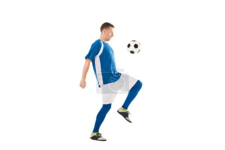 Photo for Side view of young soccer player training with ball isolated on white - Royalty Free Image
