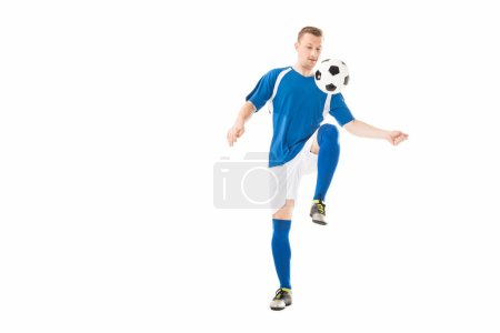 athletic young sportsman in soccer uniform training with ball isolated on white