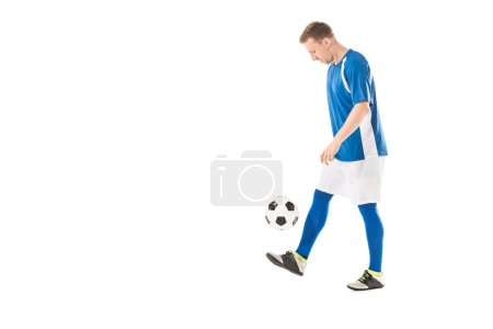 Photo for Side view of young soccer player kicking ball and looking down isolated on white - Royalty Free Image