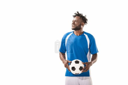 smiling african american sportsman holding soccer ball and looking away isolated on white