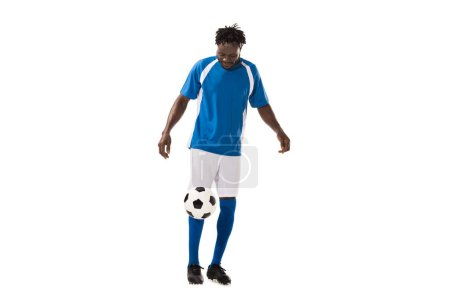 sportive african american man in soccer uniform playing with ball isolated on white