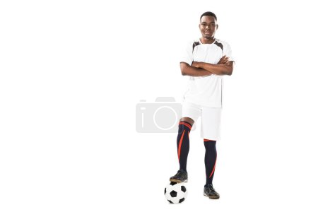 confident young african american soccer player standing with crossed arms and smiling at camera isolated on white