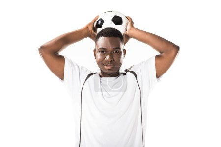 young african american soccer player holding ball above head and smiling at camera isolated on white