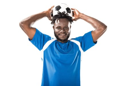 african american sportsman holding soccer ball above head and smiling at camera isolated on white
