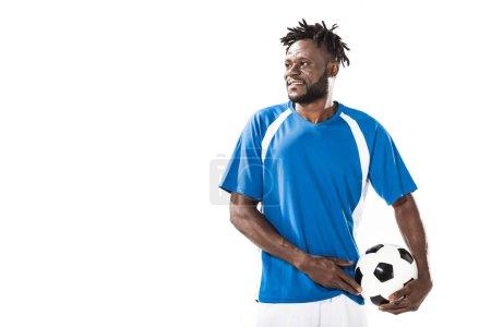 Photo pour Beau joueur de football afro-américain souriant tenant le ballon et regardant loin isolé sur blanc - image libre de droit