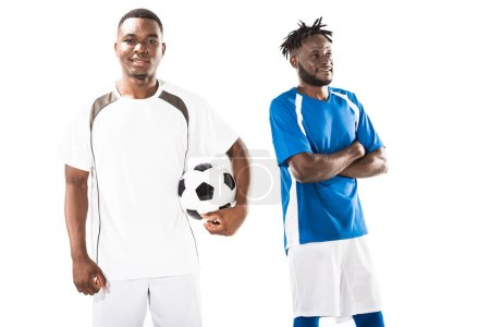 happy young african american soccer player holding ball and smiling sportsman standing with crossed arms isolated on white
