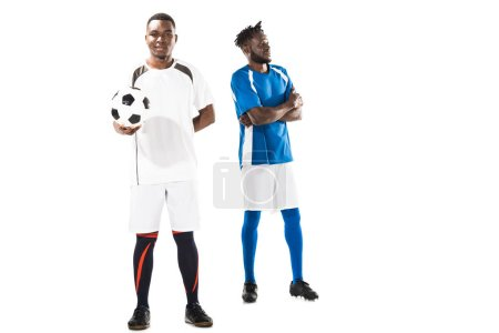 Photo for Full length view of young african american soccer player holding ball and smiling at camera while sportsman with crossed arms standing behind - Royalty Free Image