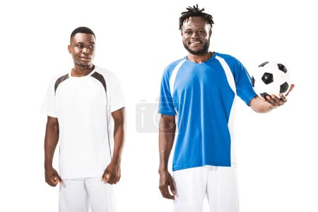 handsome smiling young african american soccer players standing with ball isolated on white