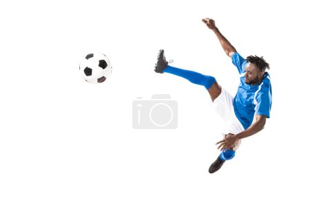 athletic african american sportsman jumping and hitting soccer ball isolated on white