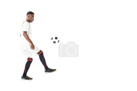 side view of handsome young african american sportsman playing with soccer ball isolated on white