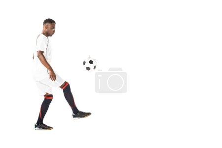Photo pour Vue latérale de beau jeune sportif afro-américain jouant avec le ballon de football isolé sur blanc - image libre de droit