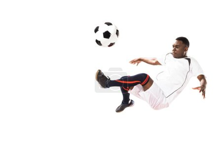 Photo for Athletic young african american soccer player kicking ball in jump isolated on white - Royalty Free Image
