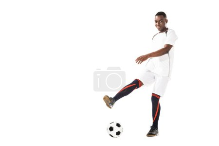 Photo for Young african american soccer player kicking ball and smiling at camera isolated on white - Royalty Free Image