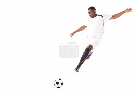 Photo for Young african american soccer player kicking ball in jump isolated on white - Royalty Free Image