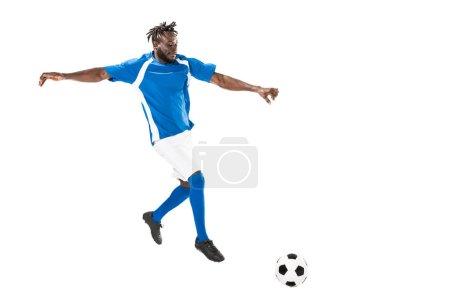Photo pour Vue de pleine longueur du footballeur afro-américain athlétique frappant le ballon isolé sur blanc - image libre de droit