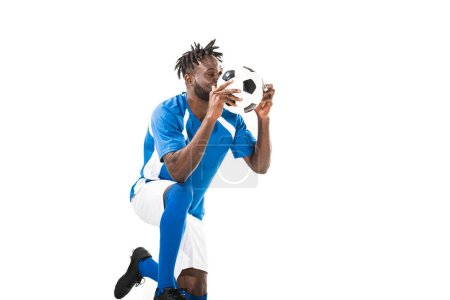 african american sportsman kneeling and holding soccer ball isolated on white