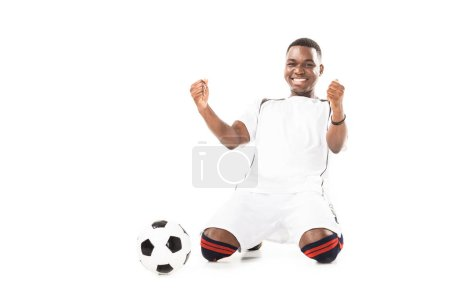 happy young african american soccer player triumphing and shaking fists isolated on white