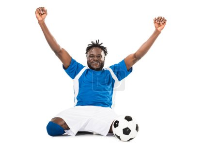excited african american soccer player triumphing and smiling at camera isolated on white