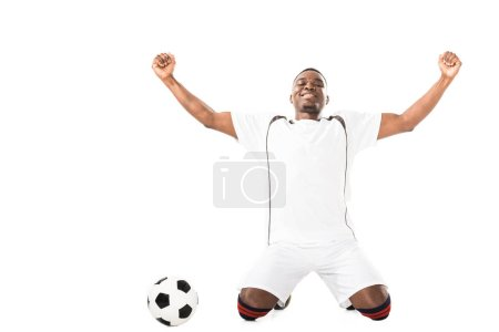 Photo for Happy young triumphing african american soccer player kneeling near ball isolated on white - Royalty Free Image