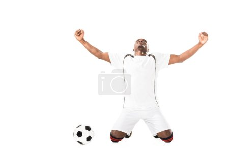 triumphing young african american soccer player kneeling near ball isolated on white