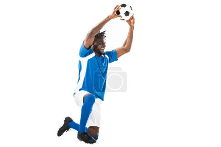 happy african american sportsman kneeling and holding soccer ball isolated on white