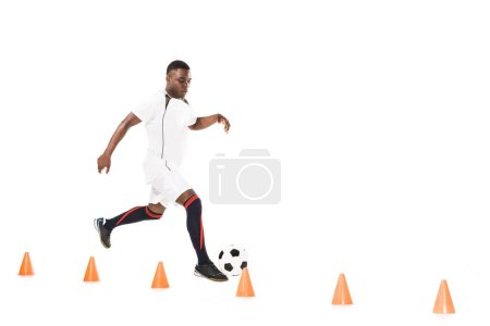 young african american sportsman running and training with soccer ball and marker cones isolated on white