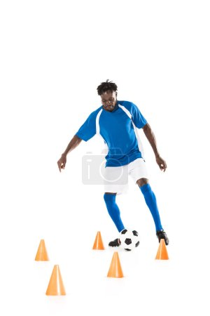 young african american sportsman training with soccer ball and marker cones isolated on white