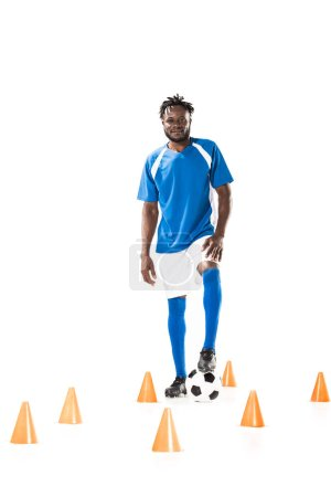 young african american sportsman standing with soccer ball between marker cones and smiling at camera isolated on white