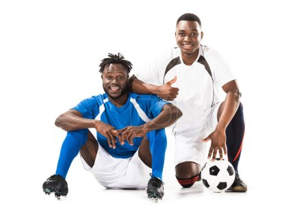 happy african american soccer players smiling at camera and showing thumb up isolated on white