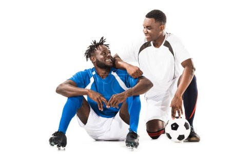 happy african american soccer players smiling each other isolated on white