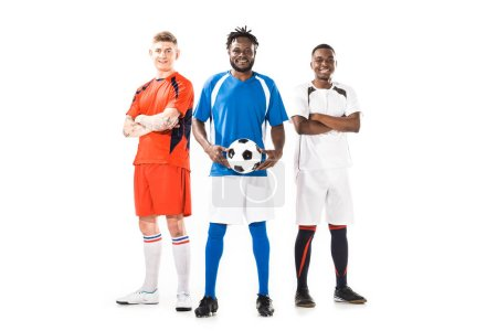 full length view of multiethnic young soccer players standing together and smiling at camera isolated on white