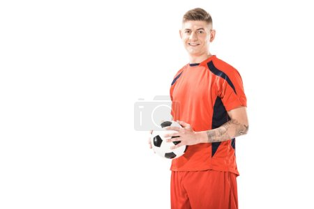 happy young athletic man in sportswear holding soccer ball and smiling at camera isolated on white