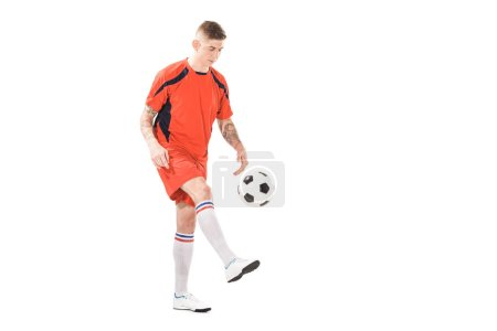 full length view of handsome young sportsman playing with soccer ball isolated on white