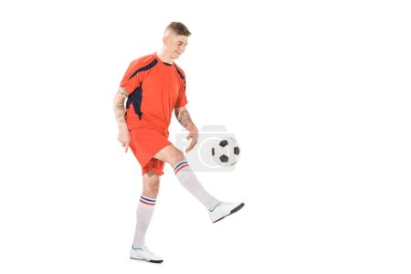 full length view of smiling young sportsman kicking soccer ball isolated on white